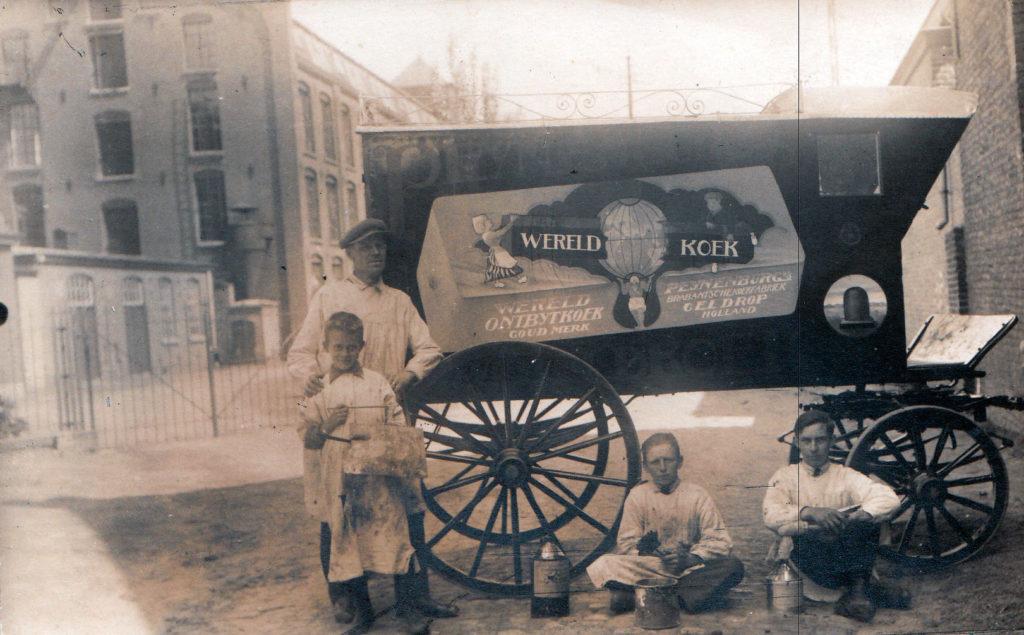 Piet Knaapen poseert met zijn zoon Frans (links) bij een kar waarop hij reclame voor Peijnenburg-koek heeft geschilderd